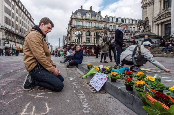 A man looks at flowers and messages outside the stock exchange in Brussels on Tuesday, March 22, 2016. Explosions, at least one likely caused by a suicide bomber, rocked the Brussels airport and subway system Tuesday, prompting a lockdown of the Belgian capital and heightened security across Europe. At least 26 people were reported dead. (ANSA/AP Photo/Geert Vanden Wijngaert)
